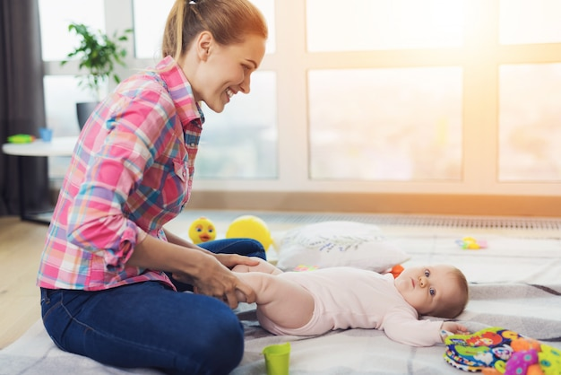 Una mujer en el piso de la sala de estar y juega con el niño. Foto Premium
