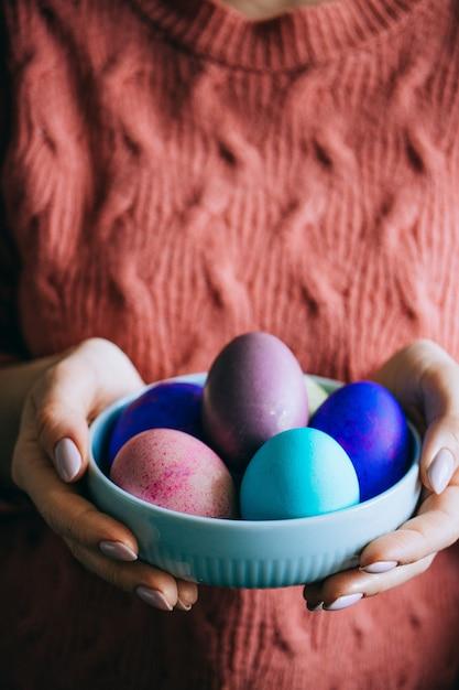 Mujer en la placa de lana coralina del asimiento del suéter con los huevos de pascua coloridos. felices pascuas Foto Premium
