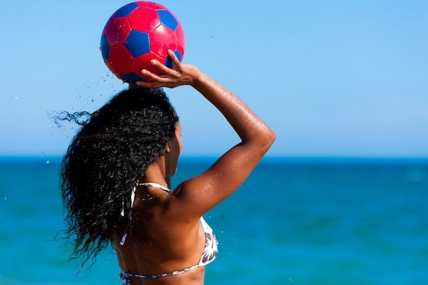 Mujer en la playa jugando futbol Foto Premium