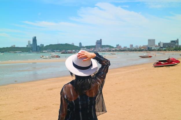 Mujer en la playa del sol mirando el mar Foto Premium