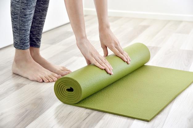 Mujer plegable yoga o colchoneta de ejercicios después de hacer ejercicio en casa, entrenamiento de ejercicio en casa. Foto Premium