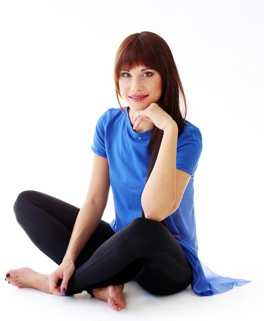 Mujer en polainas sentada en el suelo Foto gratis