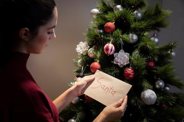 Mujer poniendo en la carta del árbol de navidad para santa claus Foto gratis
