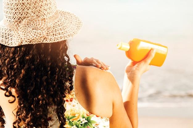 Mujer poniendo protector solar a orilla del mar Foto gratis