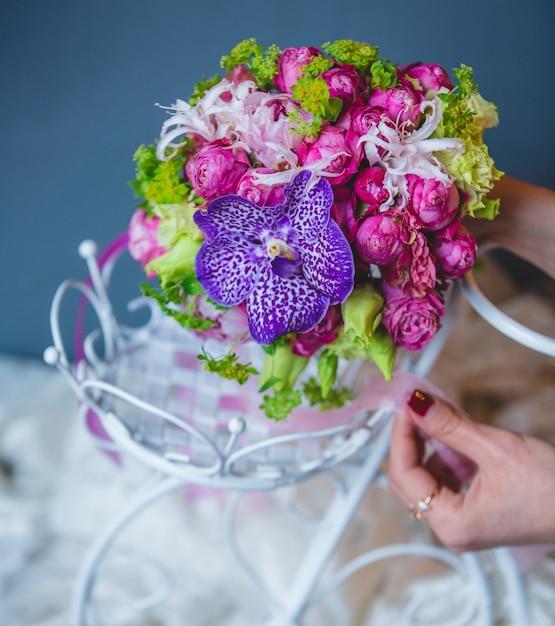 Mujer poniendo un ramo dentro del accesorio de boda blanco Foto gratis