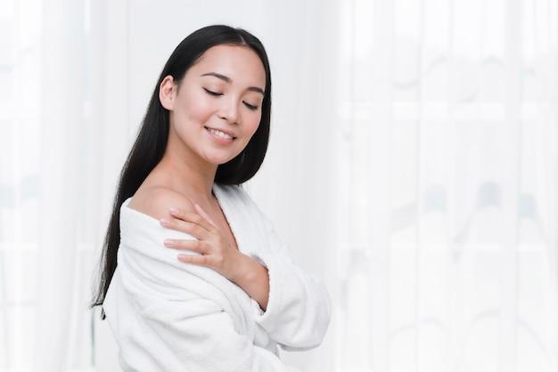 Mujer posando con albornoz en un spa Foto gratis