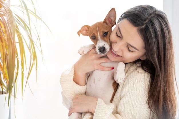 Mujer posando mientras sostiene a su perro con planta Foto gratis