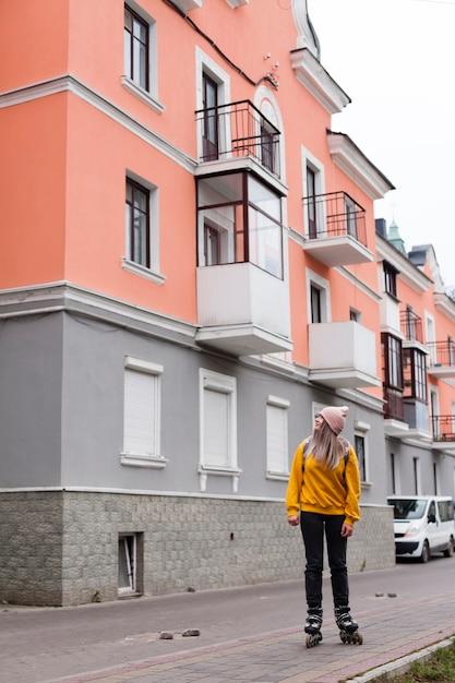 Mujer posando en patines junto a edificios Foto gratis