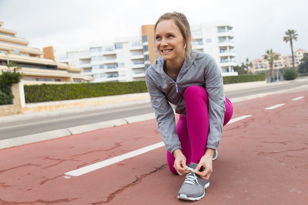 Mujer positiva en leggings de pie sobre una rodilla y atar encaje Foto gratis