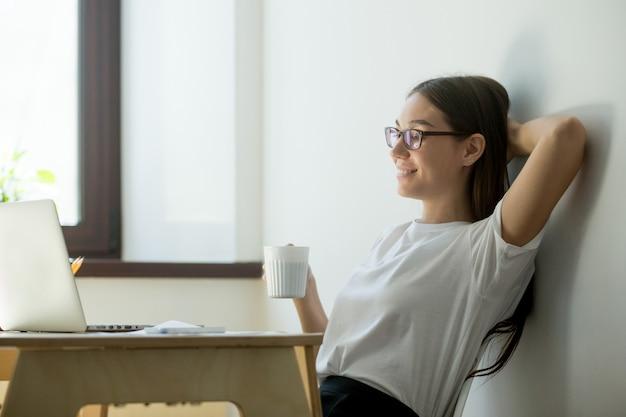 Mujer positiva milenaria relajante en el lugar de trabajo en la oficina Foto gratis