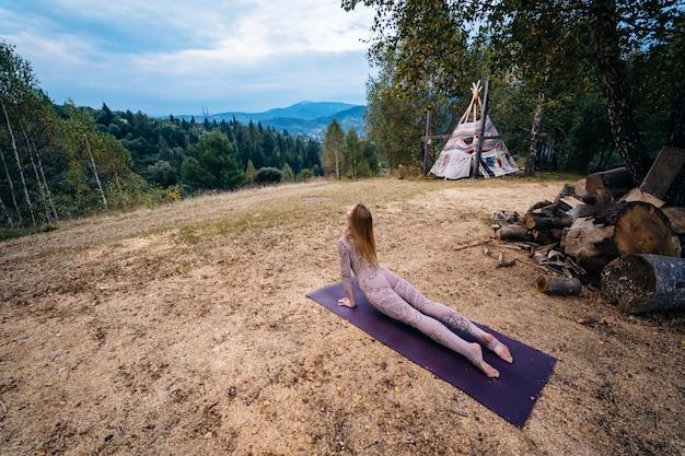 Una mujer practica yoga en la mañana en un parque al aire libre. Foto gratis
