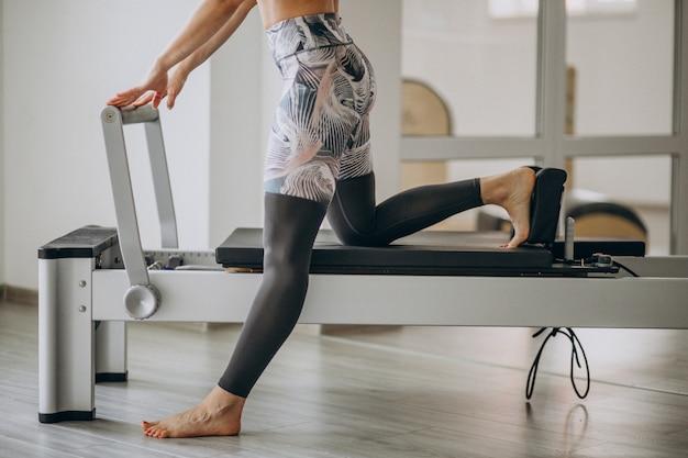 Mujer practicando pilates en una pilates reformer piernas de cerca Foto gratis