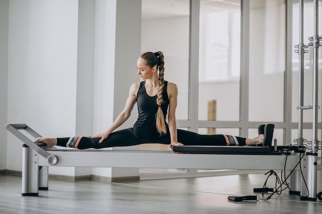 Mujer practicando pilates en un reformador de pilates Foto gratis
