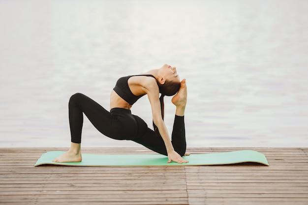 Mujer practicando yoga avanzado por el agua Foto gratis