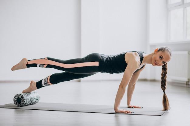 Mujer practicando yoga en una estera Foto gratis