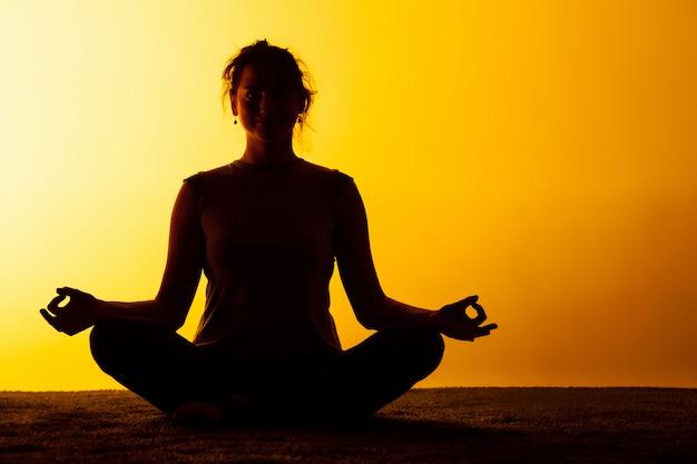 Mujer practicando yoga en la luz del atardecer Foto gratis