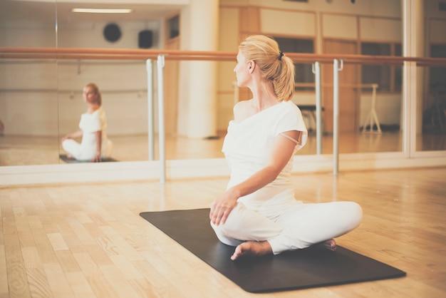 Mujer practicando yoga en la postura de giro de loto