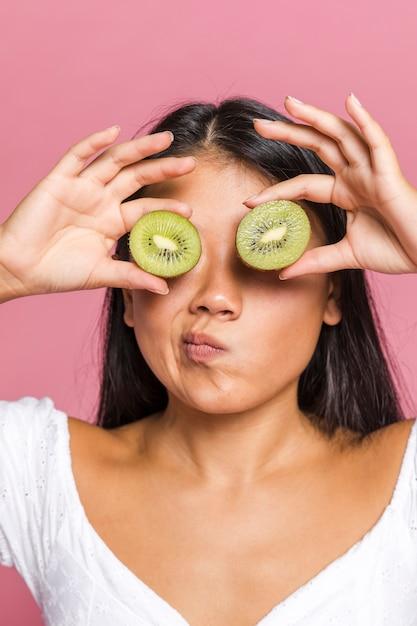 Mujer preguntándose y cubriéndose los ojos con kiwi Foto gratis