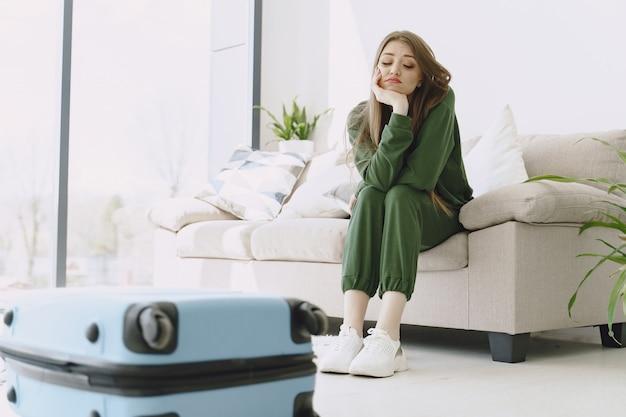 Mujer preparando maleta de viaje en casa Foto gratis