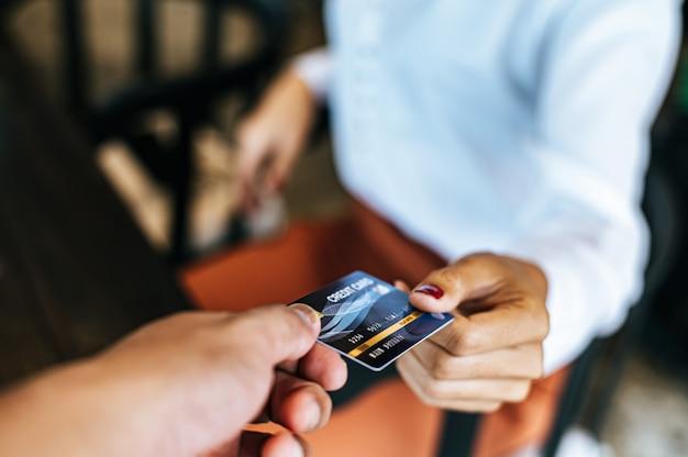 Mujer presentando tarjeta de crédito para pagar bienes Foto gratis