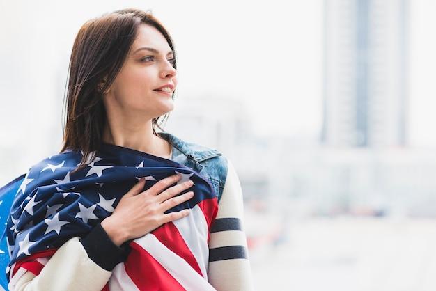Mujer presionando la bandera americana al corazón Foto gratis