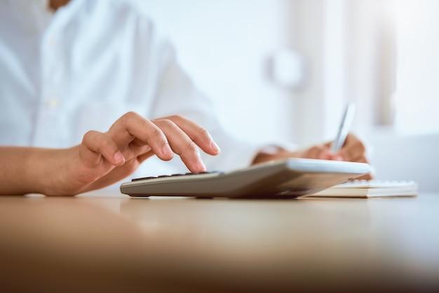 Mujer presione calculadora para calcular los gastos de ingresos y planes para gastar dinero en la oficina en casa. Foto Premium