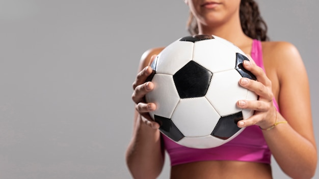 Mujer de primer plano con balón de fútbol Foto gratis