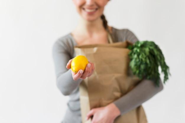Mujer de primer plano con bolsa de papel con comestibles Foto Premium