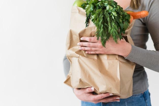 Mujer de primer plano con bolsa de papel con verduras Foto gratis