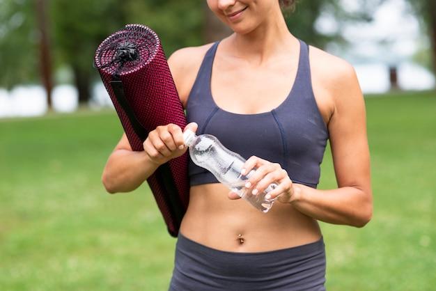 Mujer de primer plano con colchoneta de yoga y botella de agua Foto gratis