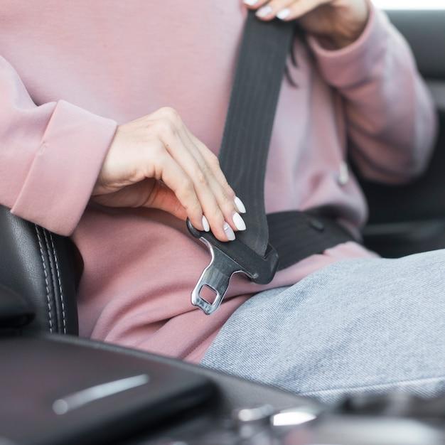 Mujer de primer plano pone su cinturón de seguridad Foto Premium