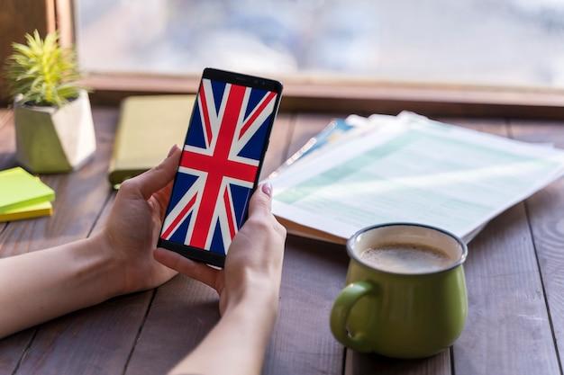 Mujer de primer plano con smartphone y taza de café Foto gratis