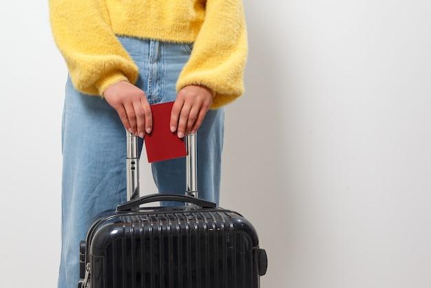 Mujer de primer plano sosteniendo un pasaporte y una bolsa de viaje en sus manos. viajes, inmigración, concepto de emigración. Foto Premium