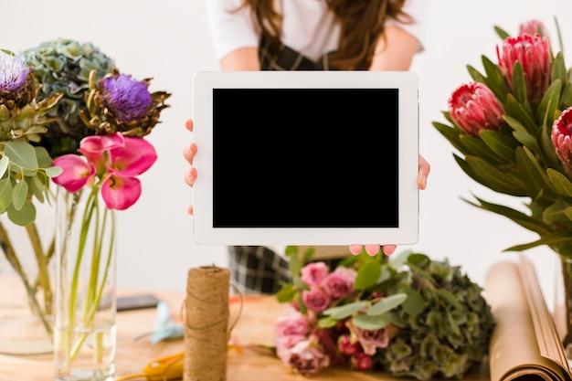 Mujer de primer plano sosteniendo una tableta en el interior Foto gratis