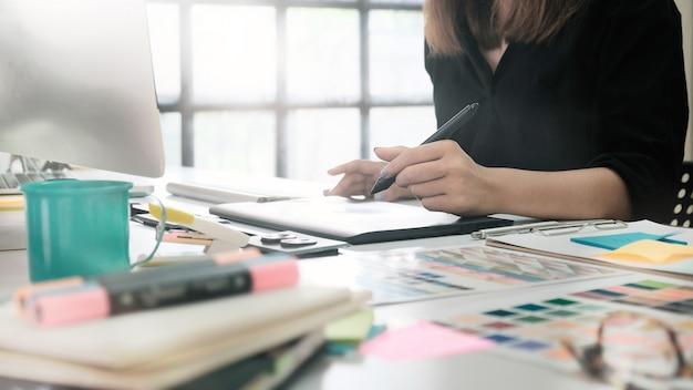 Mujer del primer que trabaja con bosquejo en la tabla digital, diseñador gráfico que trabaja en la tabla. Foto Premium
