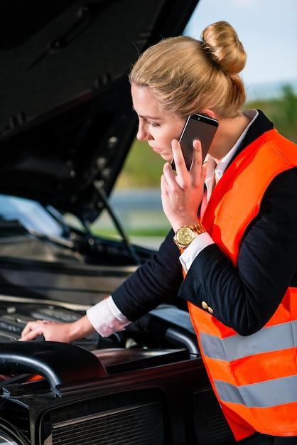 Mujer con problemas con el motor del automóvil llamando al servicio de reparación Foto Premium