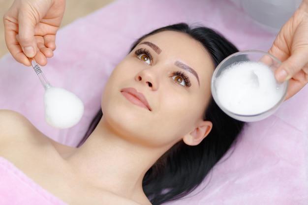 Mujer profesional aplicando crema en la cara a otra mujer Foto Gratis