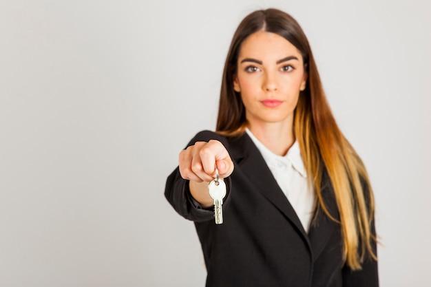 Mujer profesional entregando llaves Foto gratis