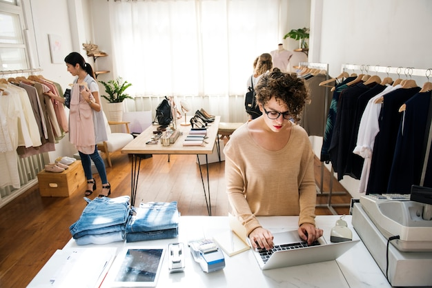Una mujer propietaria de un negocio está usando la computadora portátil. Foto gratis