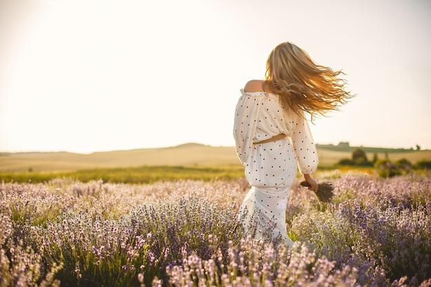 Mujer provenzal relajante en campo de lavanda. dama con un vestido blanco. niña con bouquete de flores. Foto gratis