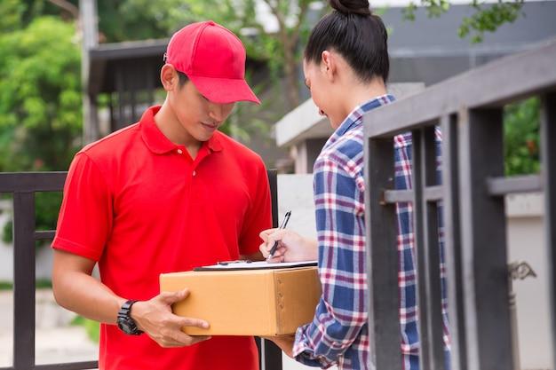 Mujer que acepta una entrega de cajas de mensajería del servicio de entrega. Foto Premium