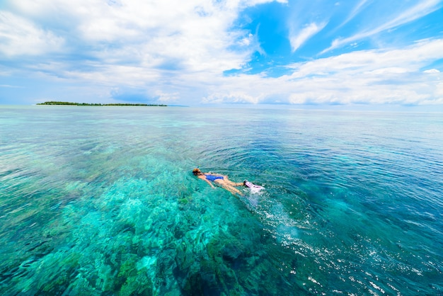 Mujer que bucea en el mar del caribe tropical del arrecife de coral, agua de azules turquesa. indonesia archipiélago de wakatobi, parque nacional marino, destino de viaje de buceo turístico Foto Premium