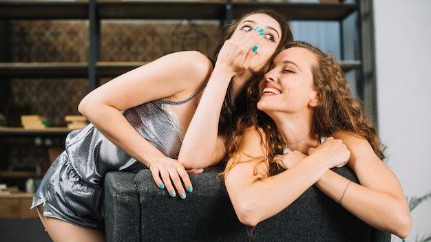 Mujer que comparte secreto con su amigo feliz Foto gratis
