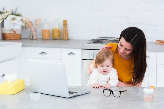 Mujer que detiene al bebé en la cocina con la computadora portátil Foto gratis