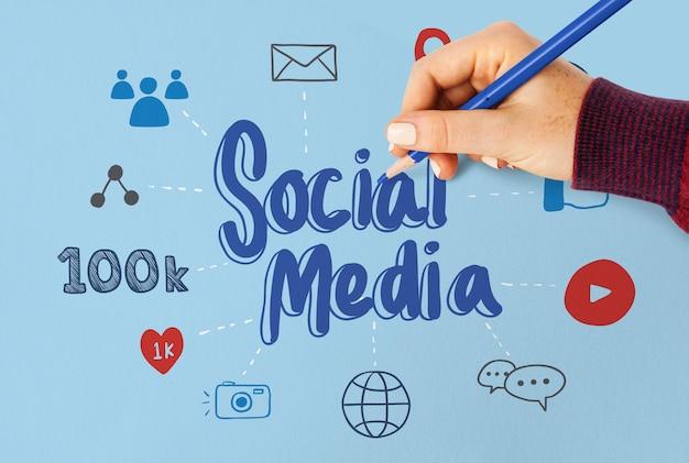 Mujer que dibuja plan de medios sociales en un papel azul Foto Premium