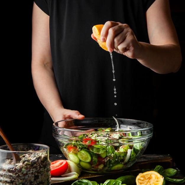 Mujer que exprime el limón en vista lateral de la ensalada gruesa. Foto gratis
