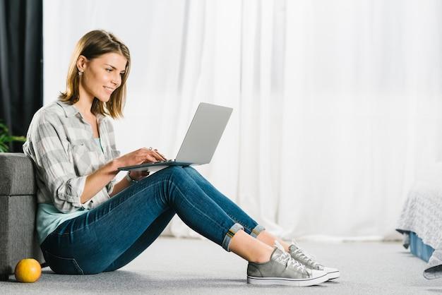 Mujer que hojea la computadora portátil en piso Foto Premium
