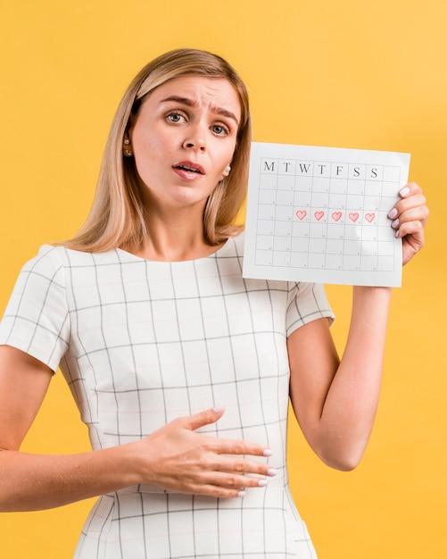 Mujer que imita los calambres estomacales de la menstruación Foto gratis
