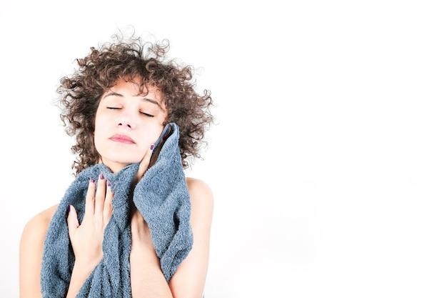 Mujer que se limpia con la toalla contra el fondo blanco Foto gratis
