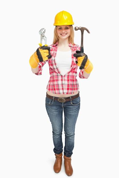 473dfc528f1 Mujer que llevaba un casco de seguridad mientras sostenía las herramientas  | Descargar Fotos premium